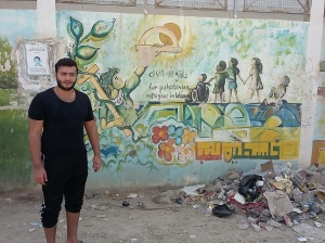 Alaa beside one of his Uncle's murals