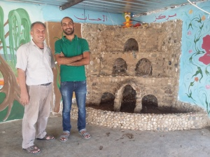 Bassel and Sheikh Abdoul beside a fountain the camp had made by hand